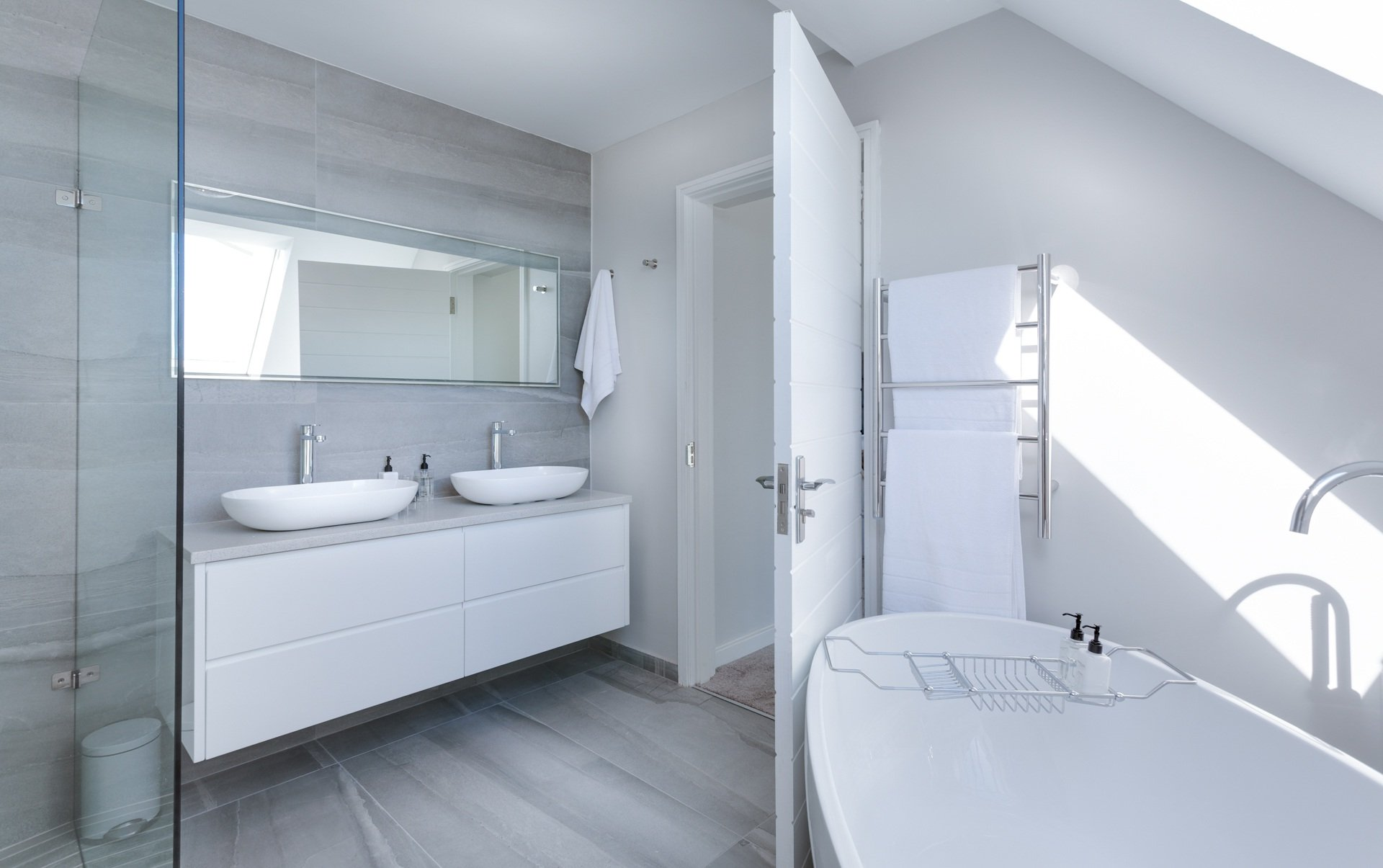 white bathroom with bath, sinks and glass shower - Noosa Plumber